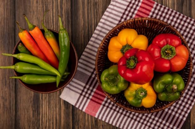 Vue de dessus de poivrons colorés frais sur un seau sur un tissu vérifié avec des poivrons verts en forme de long sur un bol sur une surface en bois