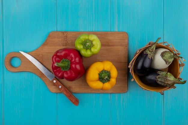 Vue de dessus poivrons colorés sur une planche à découper avec un couteau avec des aubergines blanches et noires dans un panier sur fond turquoise