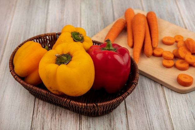 Vue de dessus des poivrons colorés sur un seau avec des carottes fraîches sur une planche de cuisine en bois sur un mur en bois gris
