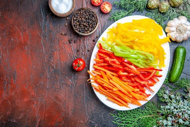 Vue de dessus poivrons coupés colorés sur plaque sel et poivre noir tomates ail concombre sur table rouge foncé espace libre