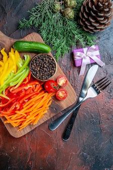 Vue de dessus poivrons coupés colorés tomates poivre noir concombre sur une planche à découper couteau et fourchette petite table rouge foncé gifton