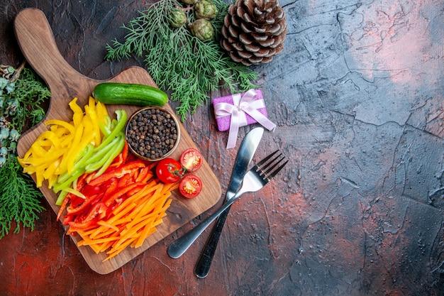Vue de dessus poivrons coupés colorés tomates poivre noir concombre sur planche à découper petit cadeau fourchette et couteau branches de pin sur table rouge foncé espace libre