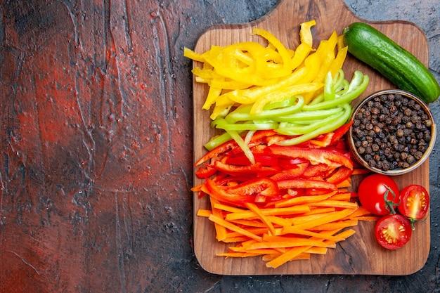 Vue de dessus poivrons coupés colorés tomates poivrons concombre sur une planche à découper sur l'espace libre de table rouge foncé