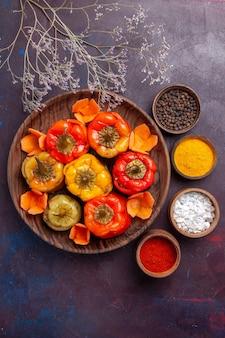 Vue de dessus poivrons cuits avec assaisonnements sur la surface gris foncé repas légumes viande dolma food