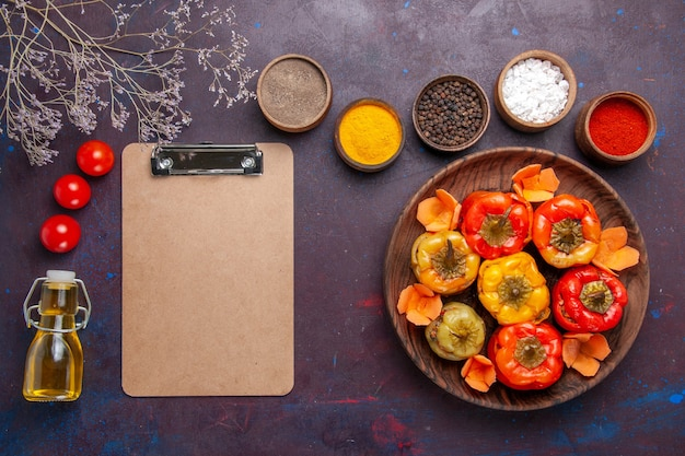 Vue de dessus poivrons cuits avec différents assaisonnements sur bureau gris foncé repas légumes viande dolma food