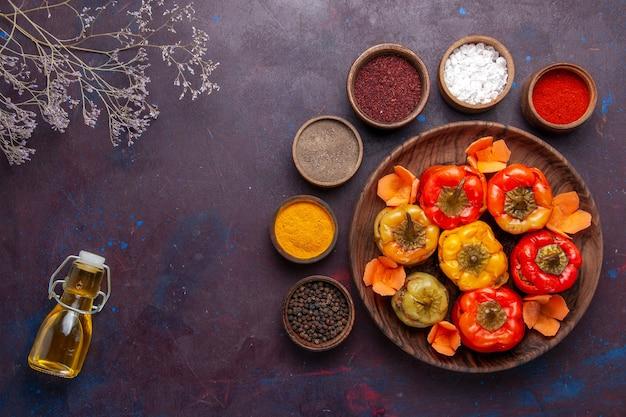 Vue de dessus poivrons cuits avec différents assaisonnements sur le bureau gris repas légumes viande dolma food