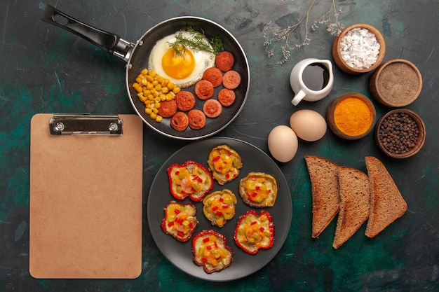 Vue de dessus poivrons cuits avec des œufs brouillés et des saucisses sur une surface vert foncé