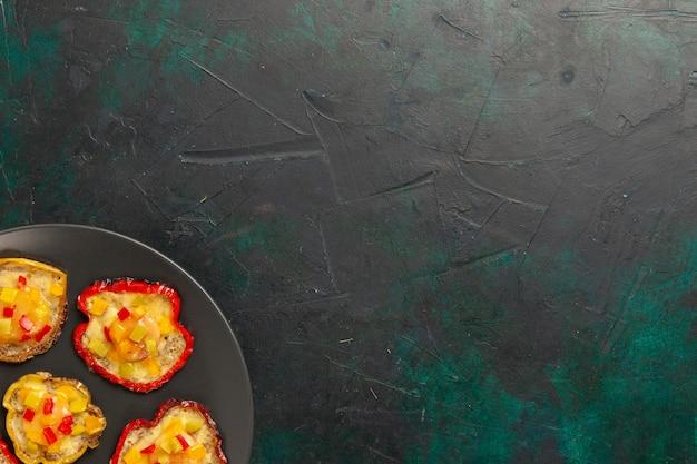Vue de dessus poivrons cuits pour le déjeuner à l'intérieur de la plaque sur le bureau sombre