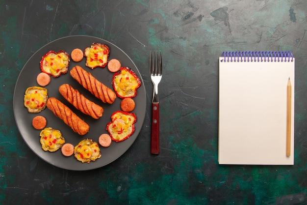 Vue de dessus poivrons cuits avec saucisses et bloc-notes sur une surface vert foncé