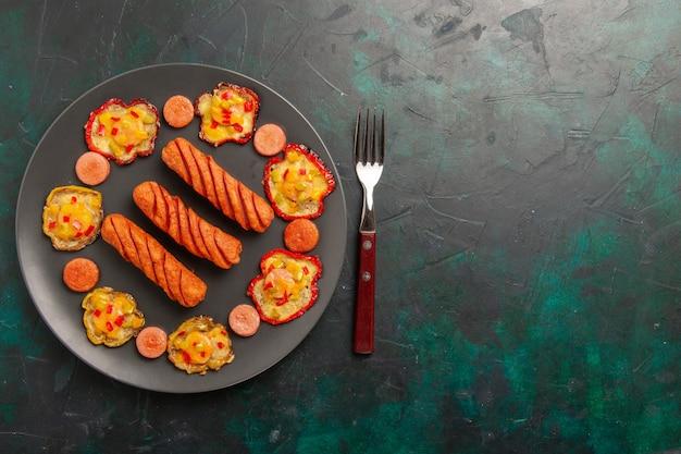 Vue de dessus poivrons cuits avec des saucisses sur un bureau vert foncé