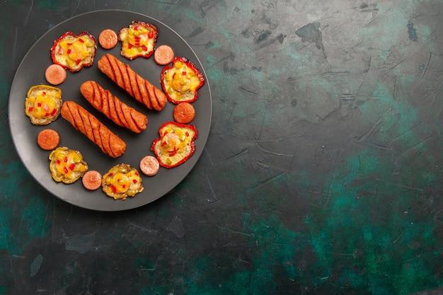Vue de dessus poivrons cuits avec des saucisses frites à l'intérieur de la plaque sur une surface vert foncé