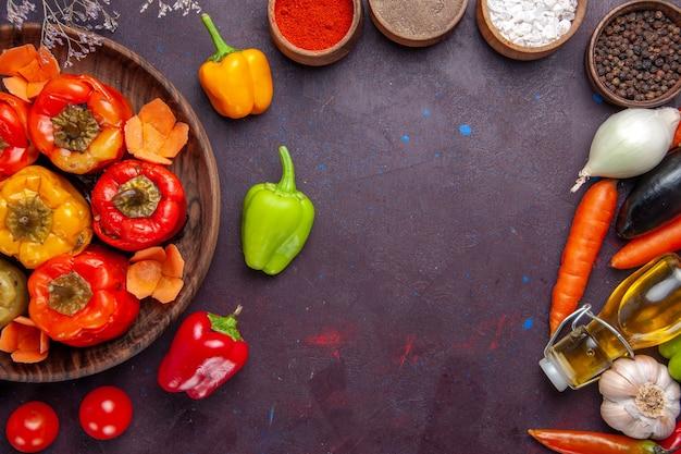 Vue de dessus des poivrons cuits avec de la viande hachée et des assaisonnements sur la surface grise repas de la viande de boeuf légumes dolma