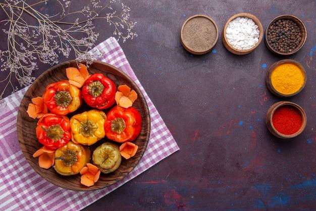 Vue de dessus des poivrons cuits avec de la viande hachée et des assaisonnements sur la surface sombre de la viande de boeuf aux légumes