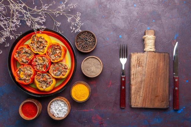 Vue de dessus poivrons cuits avec de la viande hachée et différents assaisonnements sur la surface gris foncé repas dolma nourriture légumes viande de boeuf