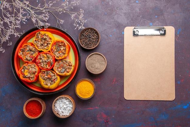 Vue de dessus poivrons cuits avec de la viande hachée et différents assaisonnements sur la surface grise repas dolma nourriture légumes viande de boeuf
