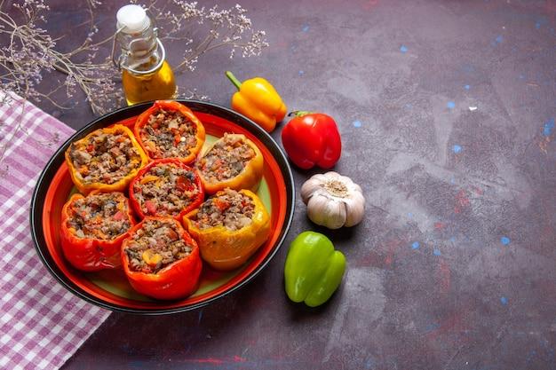 Vue de dessus des poivrons cuits avec de la viande hachée et de l'huile sur une surface sombre repas légumes nourriture viande dolma