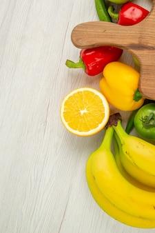 Vue de dessus des poivrons frais avec des bananes sur fond blanc couleur mûre vie saine alimentation salade photo