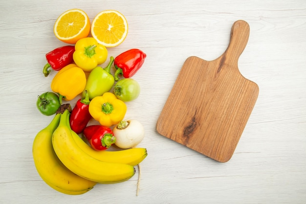 Vue de dessus poivrons frais avec bananes sur fond blanc photo fruits repas couleur salade mûre mûre