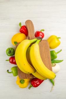 Vue de dessus des poivrons frais avec des bananes sur fond blanc régime salade vie saine photo couleur mûre