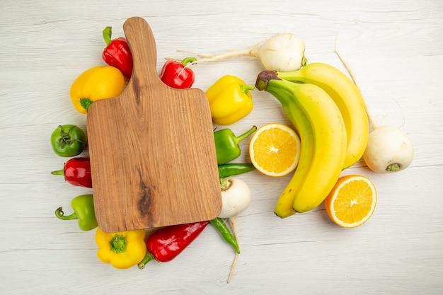 Vue de dessus des poivrons frais avec des bananes et de l'orange sur fond blanc salade vie saine couleur mûre régime