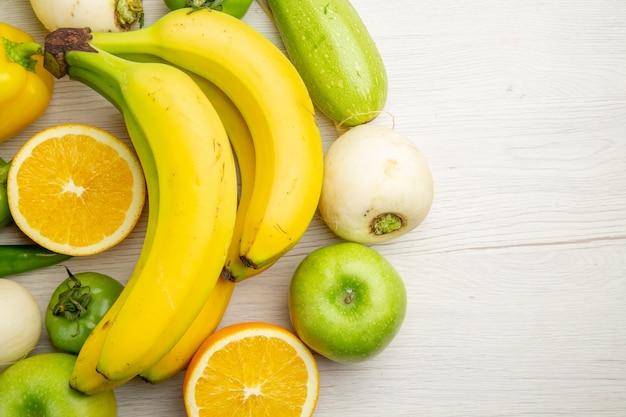 Vue de dessus des poivrons frais avec des bananes et des pommes sur fond blanc salade vie saine couleur mûre régime