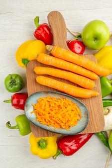 Vue de dessus des poivrons frais avec des carottes et des pommes sur fond blanc photo salade vie saine couleur mûre régime