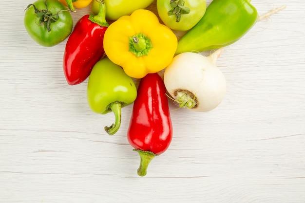 Vue de dessus de poivrons frais de différentes couleurs sur fond blanc couleur de salade de repas mûrs