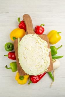 Vue de dessus des poivrons frais avec du chou sur fond blanc régime salade couleur vie saine photo mûre