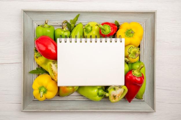 Vue de dessus des poivrons frais à l'intérieur du cadre sur un tableau blanc