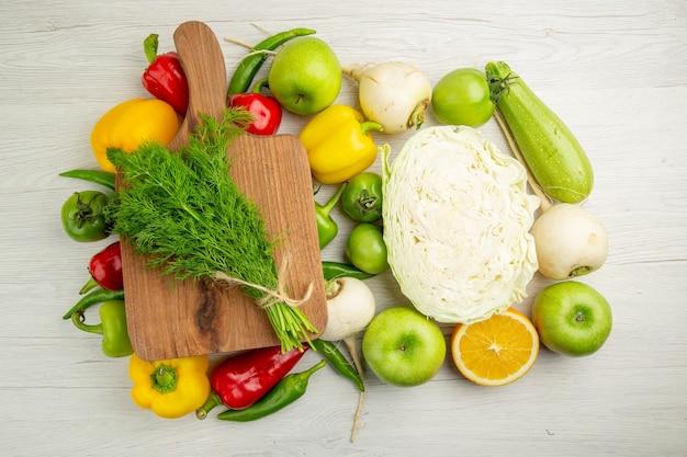 Vue de dessus poivrons frais avec pommes chou et légumes verts sur fond blanc salade de couleur mûre régime de vie sain