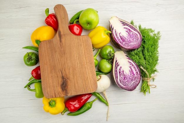 Vue de dessus des poivrons frais avec des pommes et du chou rouge sur fond blanc photo couleur mûre vie saine régime salade