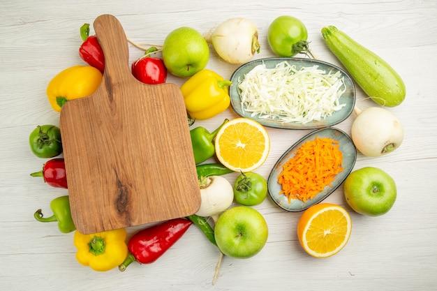 Vue de dessus des poivrons frais avec des pommes sur fond blanc couleur salade vie saine alimentation mûre