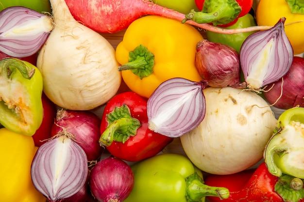 Vue de dessus de poivrons frais avec radis et oignons sur tableau blanc