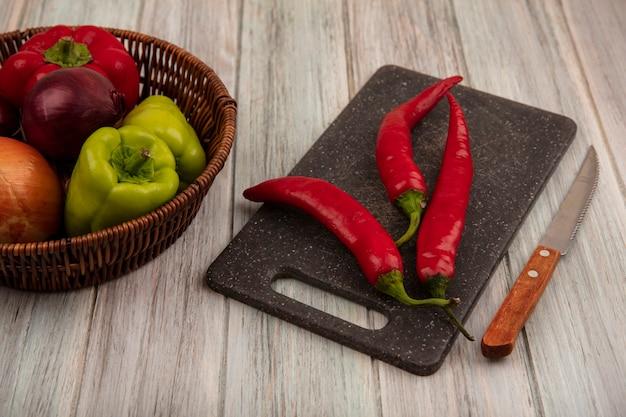 Vue de dessus de poivrons frais sur un seau avec des oignons avec des piments sur une planche de cuisine noire avec un couteau sur un fond en bois gris