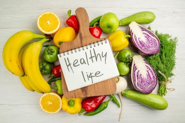 Vue de dessus des poivrons frais avec des verts et du chou rouge sur fond blanc régime couleur mûre vie saine salade photo