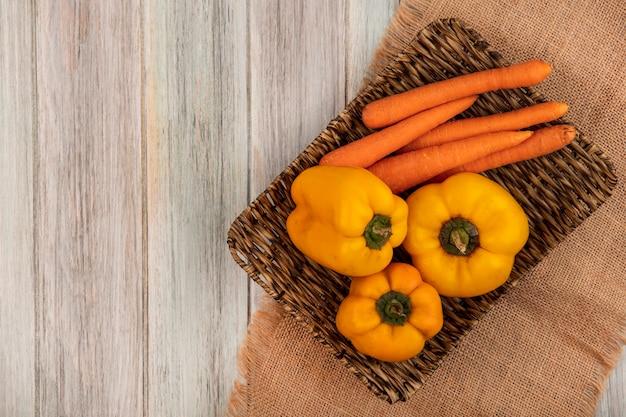 Vue de dessus des poivrons jaunes aux carottes sur un plateau en osier sur un sac en tissu sur un mur en bois gris avec espace copie