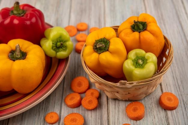 Vue de dessus des poivrons jaunes et verts frais sur un seau avec des carottes hachées isolé sur une surface en bois gris