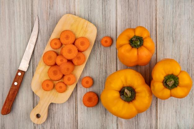 Vue de dessus des poivrons orange frais avec des carottes hachées sur une planche de cuisine en bois avec un couteau sur un mur en bois gris