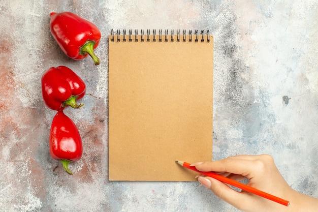 Vue de dessus poivrons rouges un crayon rouge de cahier dans la main de femme sur l'espace libre de surface nue