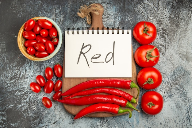 Vue de dessus poivrons rouges épicés avec tomates et écriture rouge sur fond sombre photo nourriture mûre