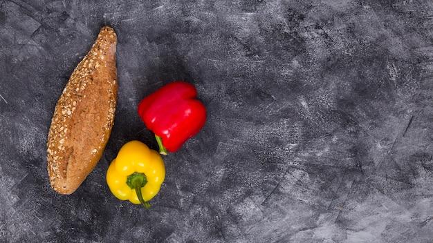 Une vue de dessus de poivrons rouges et jaunes avec une miche de pain sur un fond texturé noir