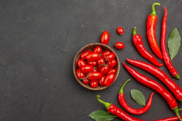 Vue de dessus les poivrons rouges et payer les feuilles et un bol de tomates cerises sur le côté droit de la table noire avec espace libre