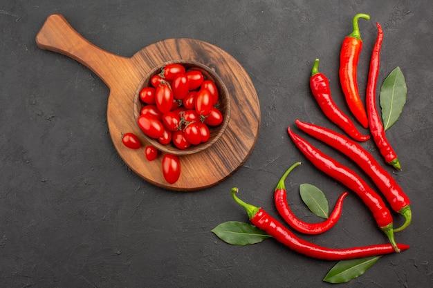 Vue de dessus les poivrons rouges et payer les feuilles et un bol de tomates cerises sur la planche à découper sur fond noir avec espace libre