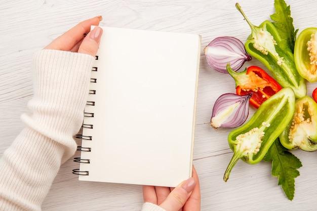 Vue de dessus de poivrons tranchés avec des oignons et une femme tenant un bloc-notes sur une table blanche