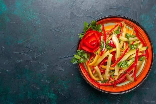 Vue de dessus poivrons tranchés salade de couleur différente à l'intérieur de la plaque sur le fond sombre