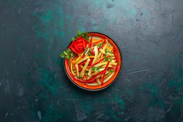 Vue de dessus poivrons tranchés salade de légumes de couleur différente à l'intérieur de la plaque sur le fond bleu foncé