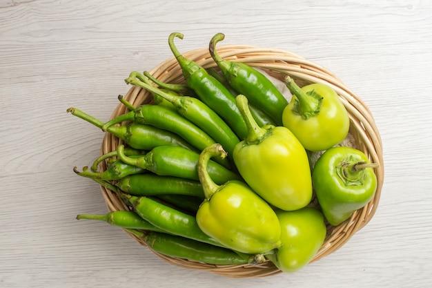 Vue de dessus des poivrons verts épicés avec des poivrons à l'intérieur du panier sur fond blanc