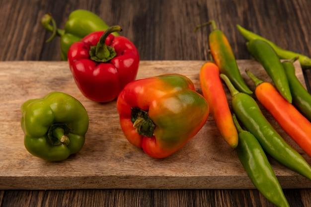 Vue de dessus des poivrons verts et orange frais isolés sur une planche de cuisine en bois sur une surface en bois
