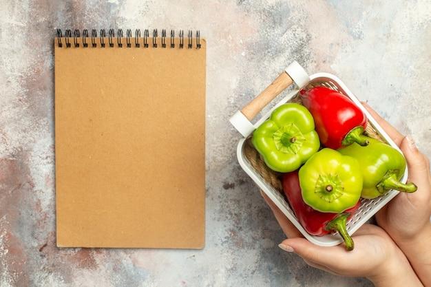 Vue de dessus poivrons verts et rouges dans un panier en plastique en main féminine un bloc-notes sur une surface nue