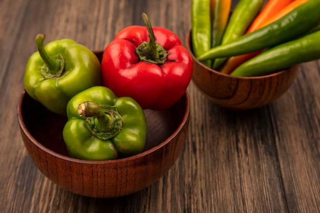 Vue de dessus des poivrons verts et rouges frais sur un bol en bois sur une surface en bois
